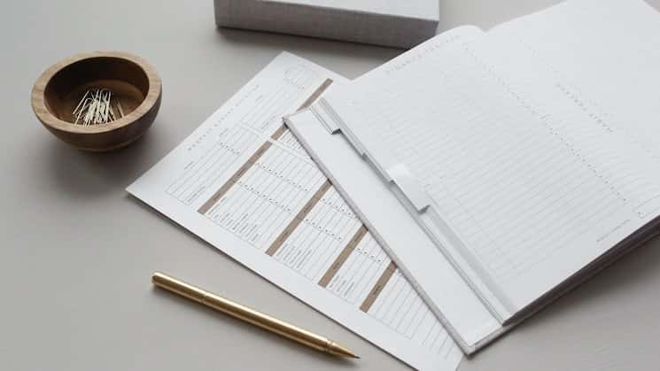 Desk with financial ledger and pen on it